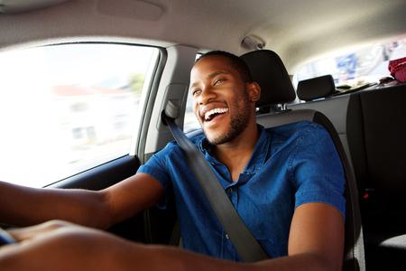 Photo pour Portrait of happy young african man enjoying driving a car - image libre de droit