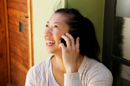 Foto für Close up portrait of smiling mature asian woman sitting outside and making a phone call - Lizenzfreies Bild