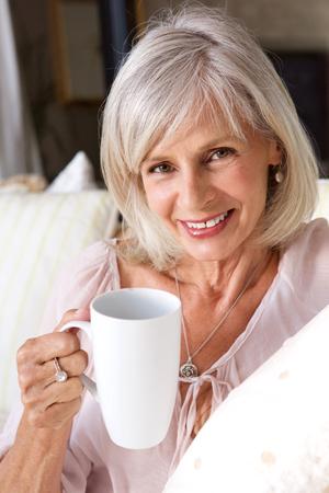 Foto de Portrait of older woman smiling with cup of coffee - Imagen libre de derechos