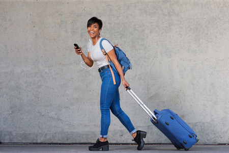 Foto de Full body portrait of young woman walking with travel bag and mobile phone - Imagen libre de derechos