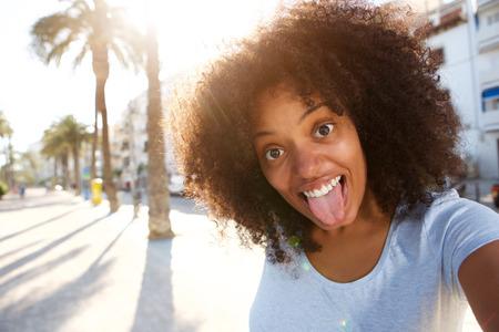 Foto de Selfie portrait of happy woman with tongue sticking out - Imagen libre de derechos