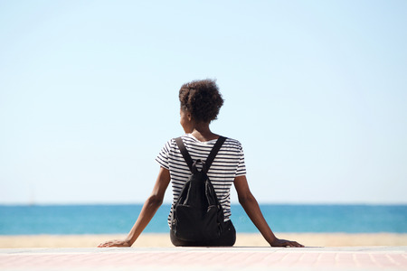 Photo for Rear view portrait of young woman sitting by the beach on summer day - Royalty Free Image