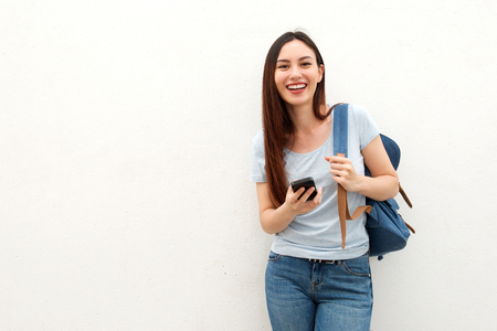 Photo pour Portrait of happy young woman standing with backpack and mobile phone - image libre de droit