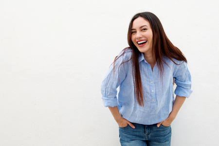 Photo for Portrait of laughing woman with long hair standing by white background - Royalty Free Image
