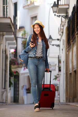 Photo pour Full length portrait of woman walking on street with luggage holding mobile phone - image libre de droit