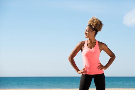 Photo pour Portrait of fit woman standing by the beach - image libre de droit