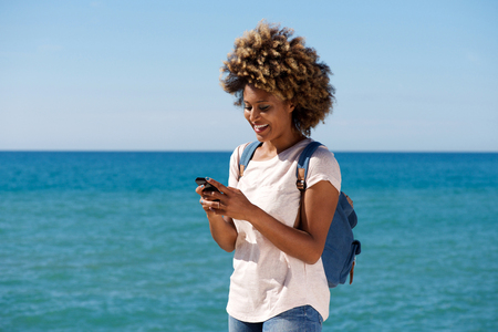 Foto de Portrait of smiling african woman on the beach reading text message on smart phone - Imagen libre de derechos