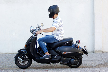 Foto de Side view portrait of young man in helmet riding a scooter on road - Imagen libre de derechos