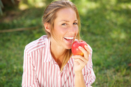 Photo for Portrait of attractive young woman eating apple in the park - Royalty Free Image