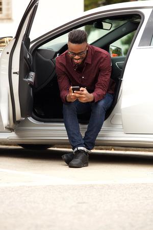 Foto de Portrait of african american man sitting in car sending text message - Imagen libre de derechos