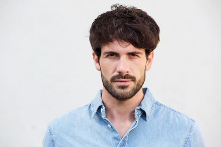 Foto de Close up portrait of handsome young man with beard against white background - Imagen libre de derechos