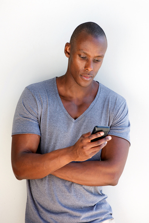 Photo for Portrait of cool black guy leaning against wall using mobile phone - Royalty Free Image