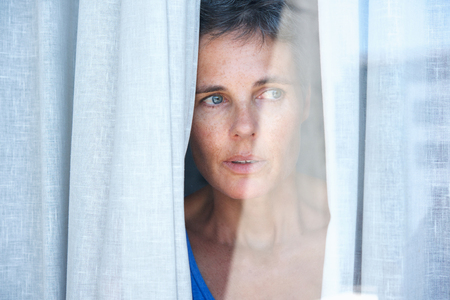 Photo for Close up portrait of older woman looking opening curtains and looking through window - Royalty Free Image