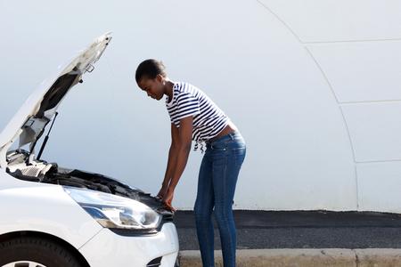 Foto de Side portrait of young african american woman looking under the hood of broken down car - Imagen libre de derechos