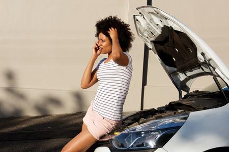Foto de Side portrait of young woman standing by broken down car and making phone call for assistance - Imagen libre de derechos