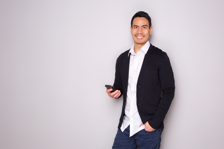 Photo for Portrait of handsome mature man with phone on gray background - Royalty Free Image