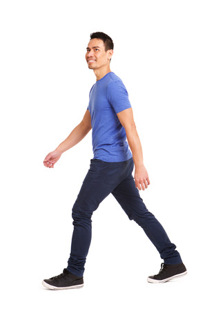 Photo for Full length side portrait of happy asian man walking over white background - Royalty Free Image