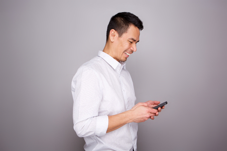 Photo pour Portrait of smiling middle aged man reading text message on his mobile phone on gray background - image libre de droit