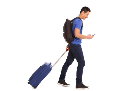 Photo for Full body side portrait of smiling mature man walking with suitcase and cellphone on white background - Royalty Free Image