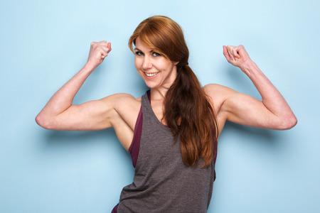 Photo pour Portrait of happy mature woman flexing bicep muscles against blue wall - image libre de droit