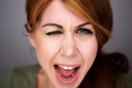 Photo pour Close up portrait of cheerful middle aged woman winking eye - image libre de droit