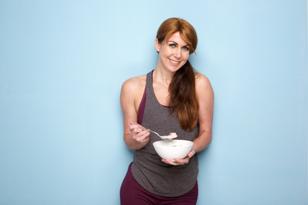 Photo for Portrait of attractive middle aged woman with muscular and fit body eating healthy breakfast - Royalty Free Image