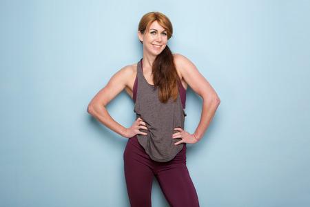 Photo pour Portrait of muscular mature woman standing against blue wall with hands on hips - image libre de droit