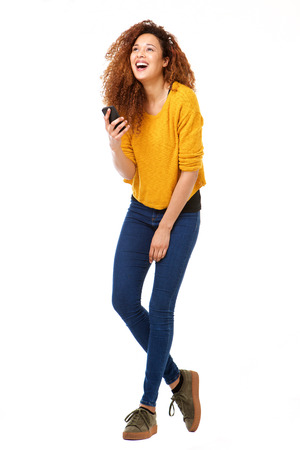 Foto de Full body portrait of happy woman with smart phone laughing against isolated white background - Imagen libre de derechos
