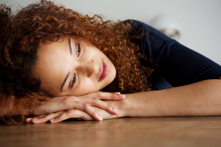 Photo for Close up portrait of tired young woman resting on table - Royalty Free Image