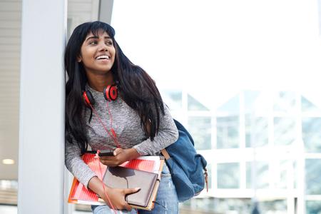 Photo pour Portrait of smiling female student with mobile phone, books and bag - image libre de droit