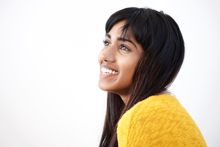 Close up side portrait of cheerful young Indian woman against isolated white background