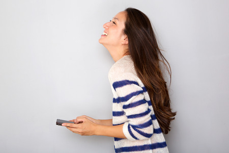 Side portrait of pretty asian woman smiling with smart phone against gray background