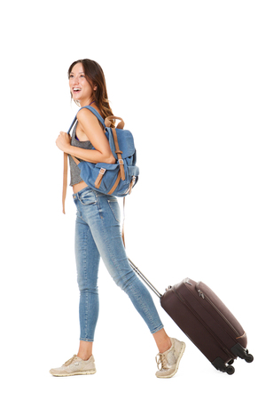 Photo pour Full body side portrait of young asian woman walking against isolated white background with suitcase and bags - image libre de droit