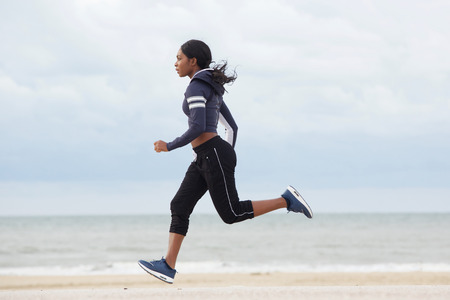 Photo pour Full body side portrait of sporty young black woman running by the beach - image libre de droit