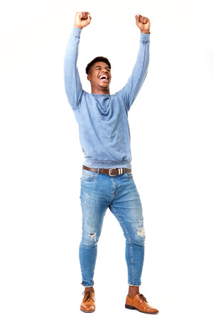 Photo pour Full body portrait of cheerful young black man with arms raised against isolated white background - image libre de droit