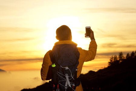 Photo for Portrait from behind of man with backpack taking selfie during sunset - Royalty Free Image