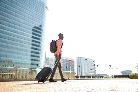 Photo pour Full length portrait of young black man walking with suitcase in city - image libre de droit