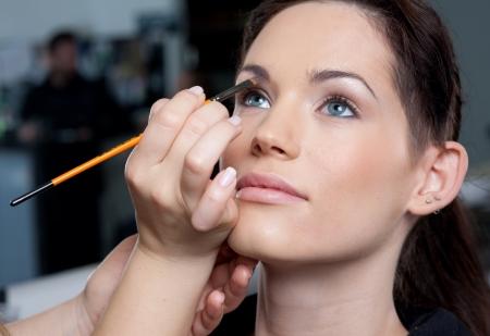 Make up artist applying make up to a fashion model/bride