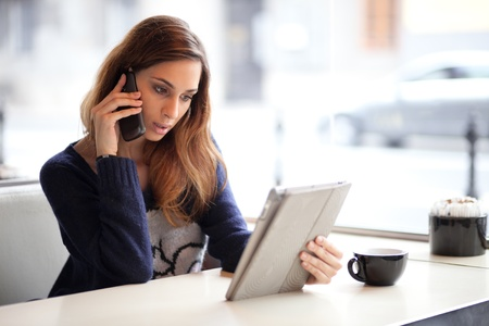 Candid image of a young woman talking on the phone in a cafe  Selective focus