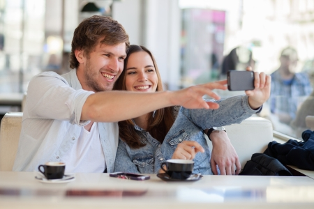 Foto de Young couple taking a photo of themselves in a cafe - Imagen libre de derechos