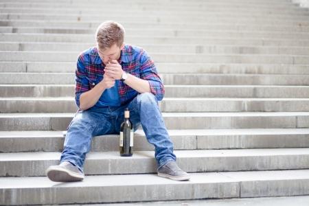 Foto de Drunk young man lighting a cigarette on the stairs - Imagen libre de derechos
