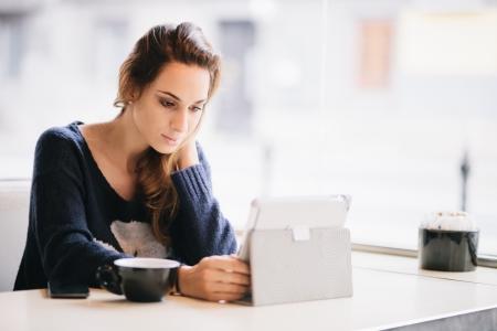 Foto de Young woman   student using tablet computer in cafe - Imagen libre de derechos