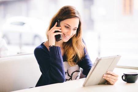 Foto de Happy young woman talking on the phone in a cafe - Imagen libre de derechos
