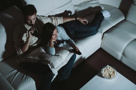 Foto de Young couple watching TV at home at night - Imagen libre de derechos
