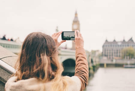 Photo pour Young woman taking a photo with her phone in London - image libre de droit