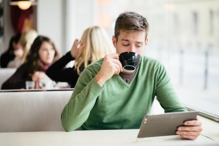 Foto de Young man drinking coffee in cafe and using tablet computer - Imagen libre de derechos