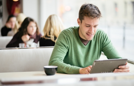 Photo for Young man   student using tablet computer in cafe - Royalty Free Image