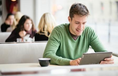 Foto de Young man   student using tablet computer in cafe - Imagen libre de derechos