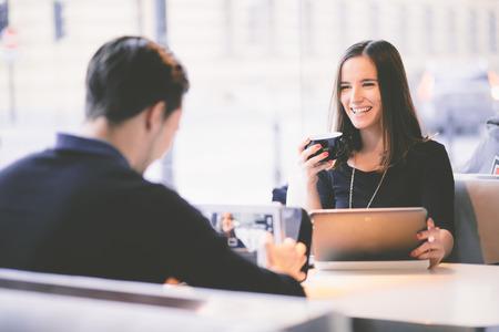 Foto de Young man taking picture of girlfriend with tablet computer in cafe - Imagen libre de derechos