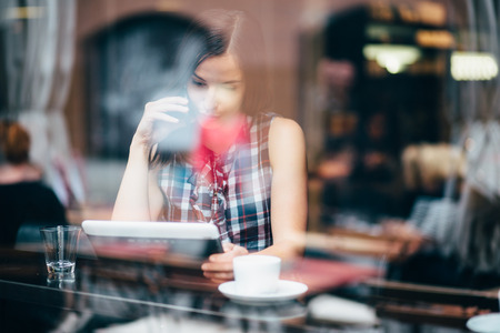 Photo for Young woman talking on phone and using tablet computer in coffee shop - Royalty Free Image
